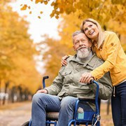 Woman with her elderly father in wheelchair outdoors on autumn day